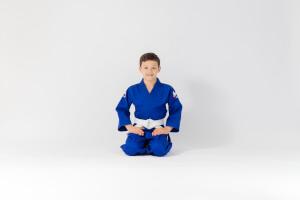 Siedzący chłopiec w niebieskiej judodze uone