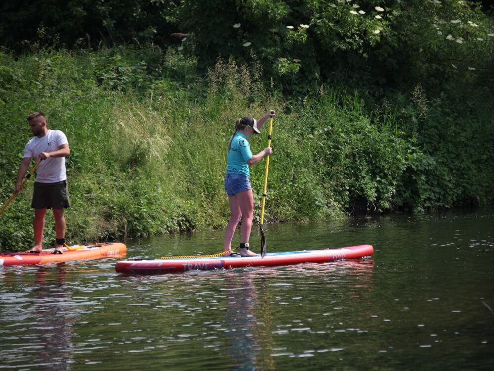 Deska SUP Traveler i wiosło z włókna szklanego marki Uone na wodzie
